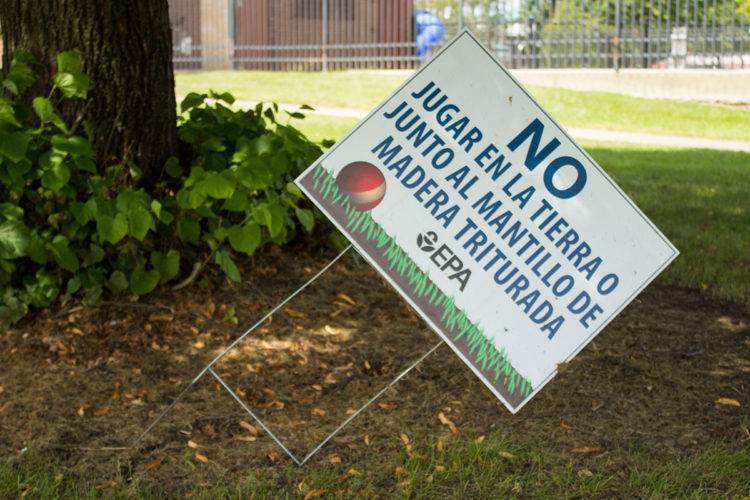 A sign from the Environmental Protection agency warns residents not to play in the soil, which is contaminated with lead and arsenic. (Lauren Chapman/IPBS)