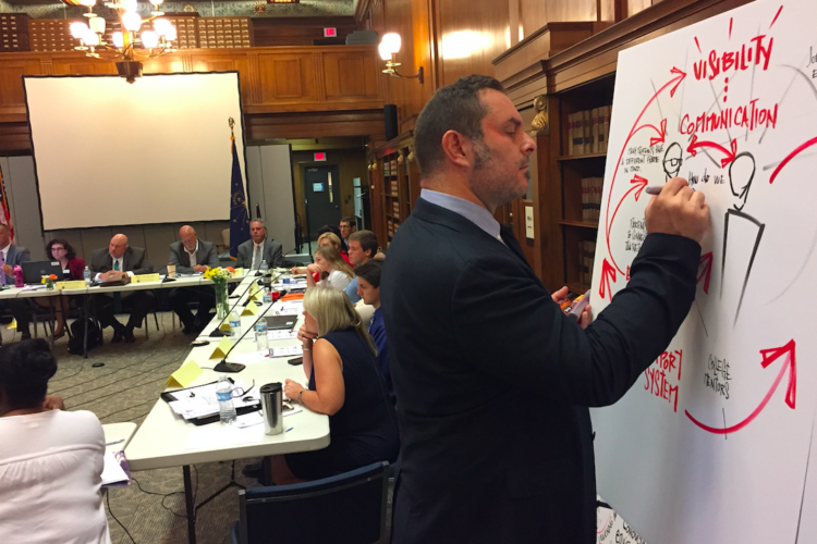 Mike Fleisch illustrates and takes notes on the discussion by the Graduation Pathways Committee members Aug. 23, 2017 at the Indiana State Library in Indianapolis. (Credit: Eric Weddle/WFYI Public Media)