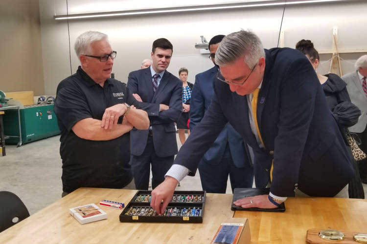 Gov. Eric Holcomb examines pens made by a teacher at the Purdue Polytechnic Institute in Anderson. (Samantha Horton/IPB News)