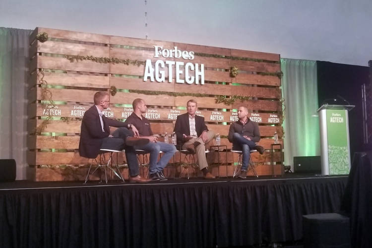 (From left to right) Reynolds Farm Equipment CEO Mitch Frazier talks with panelists AgNext CEO Troy Fiechter, farmer Jim Kline, and Taranis head of marketing Alex Whitley during Forbes AgTech Summit in Indianapolis. (Samantha Horton/IPB News)