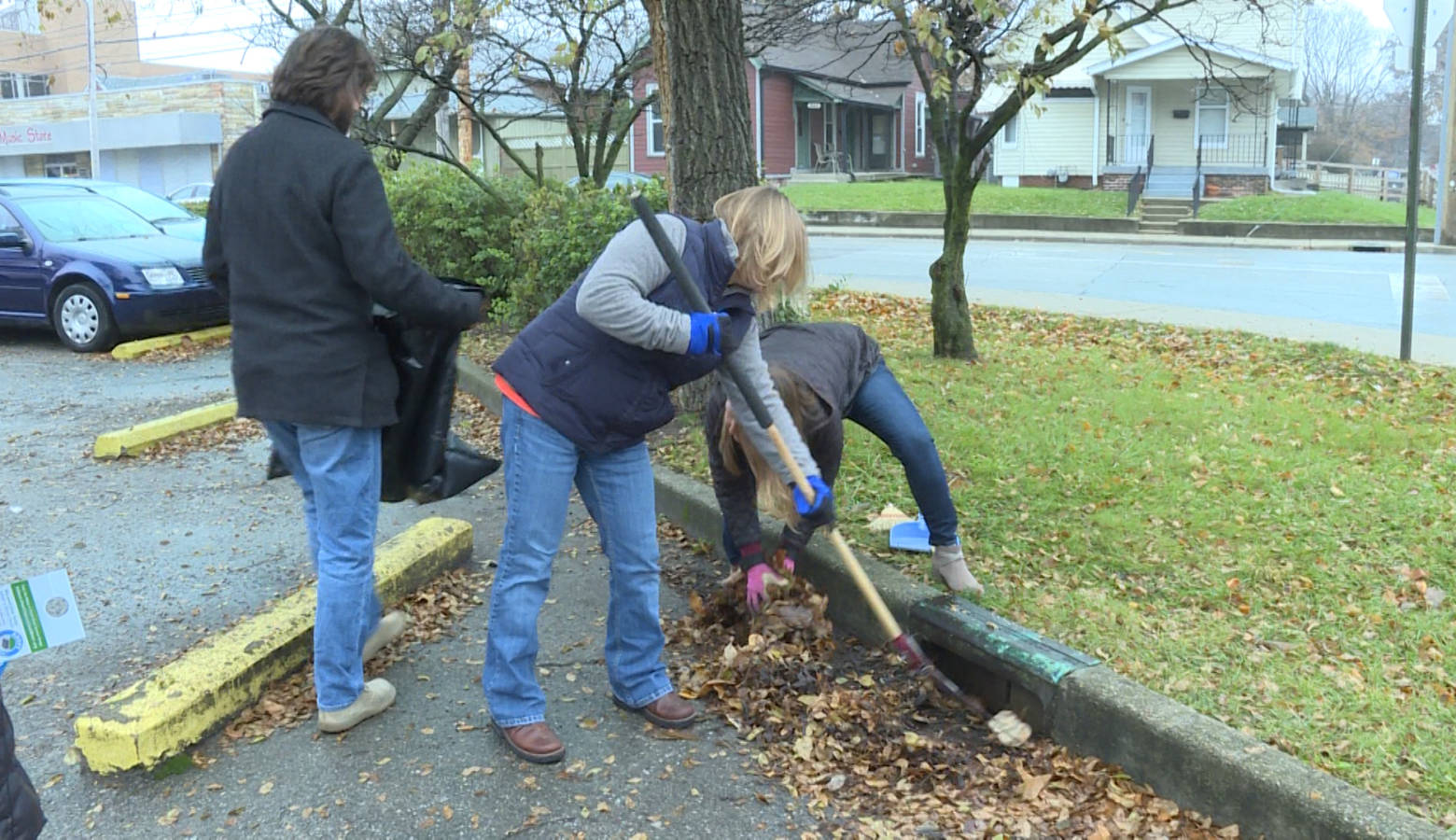 White River Alliance staff cleaning out a storm drain in the organization's office parking lot (Rebecca Thiele/IPB News)