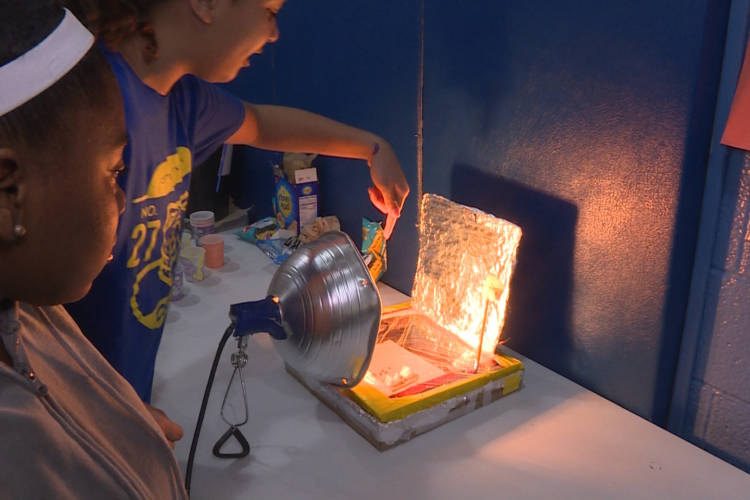 Seventh graders Tamyah Conner (left) and Bella Rollins (right) of Center for Inquiry School 27 in Indianapolis made a solar oven for the school's climate fair in March. (Rebecca Thiele/IPB News)