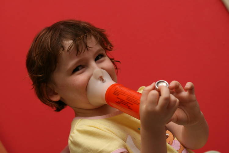 A child uses a spacer with an inhaler to treat asthma symptoms. Rising temperatures make the ozone and particle pollution that contribute to asthma problems worse (Wikimedia Commons)
