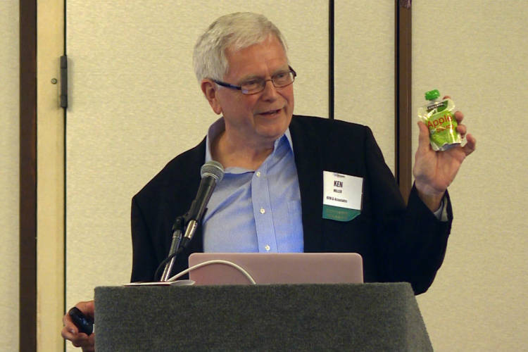 Ken Miller of KFM & Associates holds up a baby food pouch. He says because of the multiple kinds of plastic, it's one of the least recyclable products today (Rebecca Thiele/IPB News)