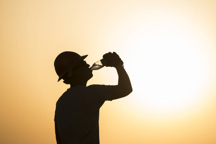 A U.S. airman drinks water while working on a construction site in extreme heat in Southwest Asia, 2017. (U.S. Air Force/Damon Kasberg)