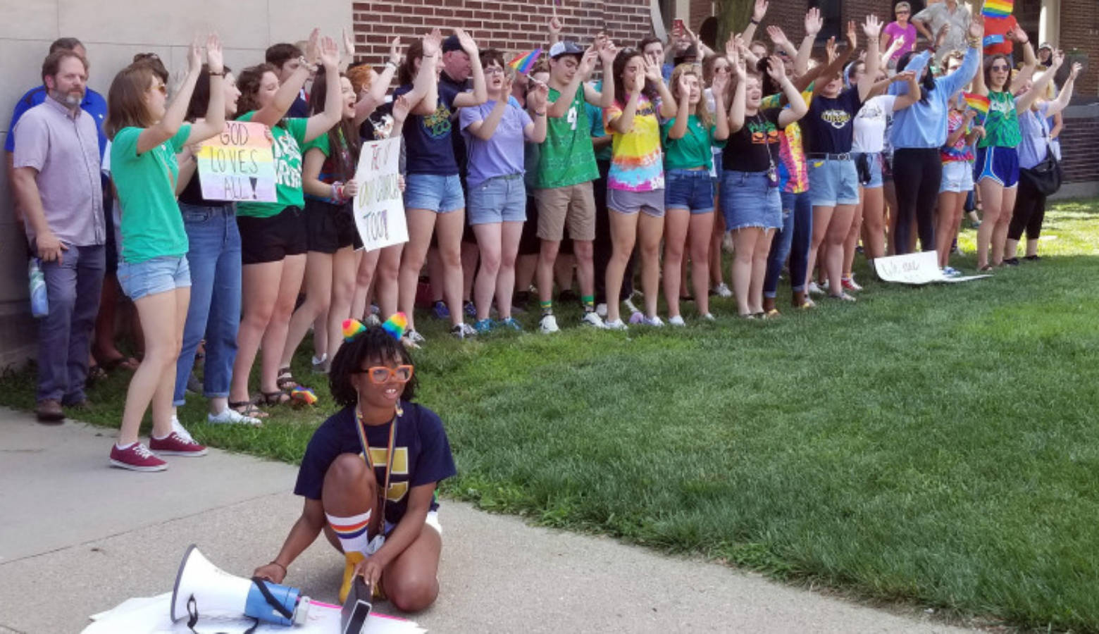 Student organizer Brooklynn Thorpe uses a megaphone to amplify music as fellow students lead school chants and cheers outside of the Archdiocese of Indianapolis during a protest Thursday, June 27, 2019.