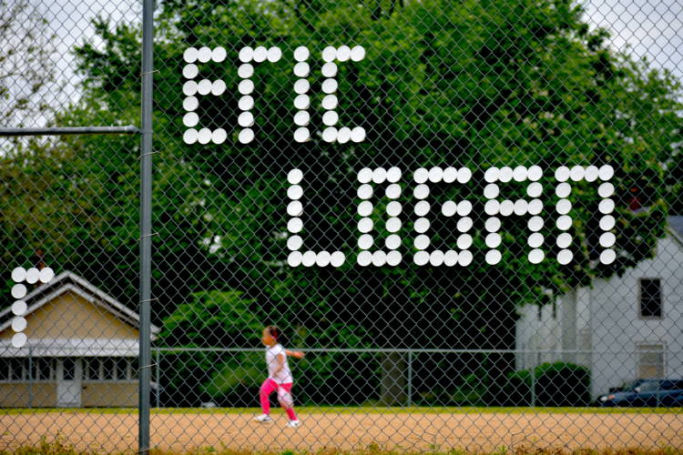 Eric Logan's name written in styrofoam cups on a fence surrounding a baseball field in South Bend. (Justin Hicks/IPB News)