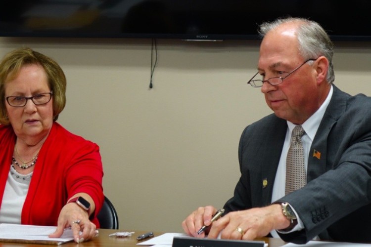 Daleville Community School's Board President Diane Evans, left, and Superintendent Paul Garrison look at documents before the school board votes to close Indiana Virtual School and Indiana Virtual Pathways Academy during a board meeting Monday, Aug. 26, 2019 at the district office.