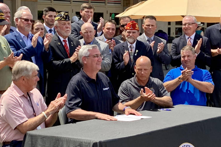 Gov. Eric Holcomb, seated center, at a ceremonial bill signing for the military pension tax exemption. (Brandon Smith/IPB News)