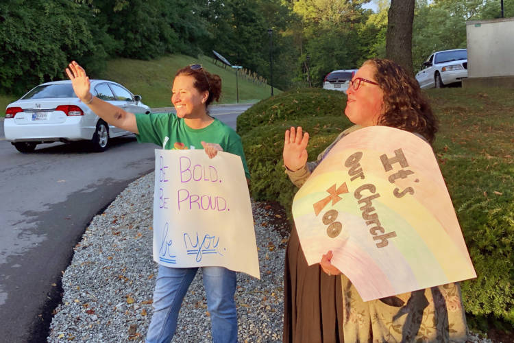 Shelly Fitzgerald waves to students entering Cathedral High School's campus. Fitzgerald was a guidance counselor as Roncalli High School before being put on administrative leave last year due to her same-sex marriage. (Darian Benson/WFYI)