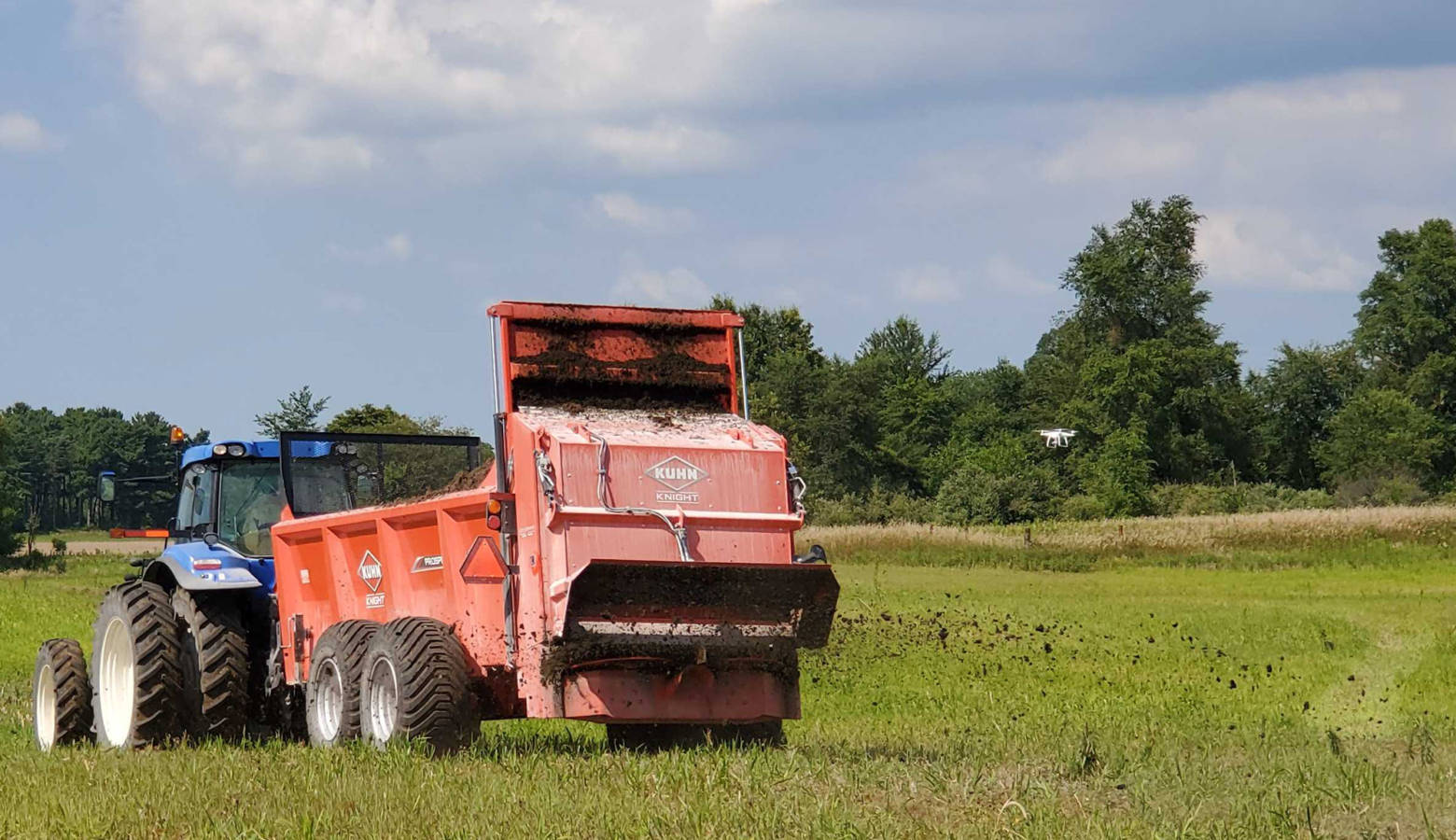 Companies demonstrate their solid manure spreaders out in the field to expo attendees. (Samantha Horton/IPB News)