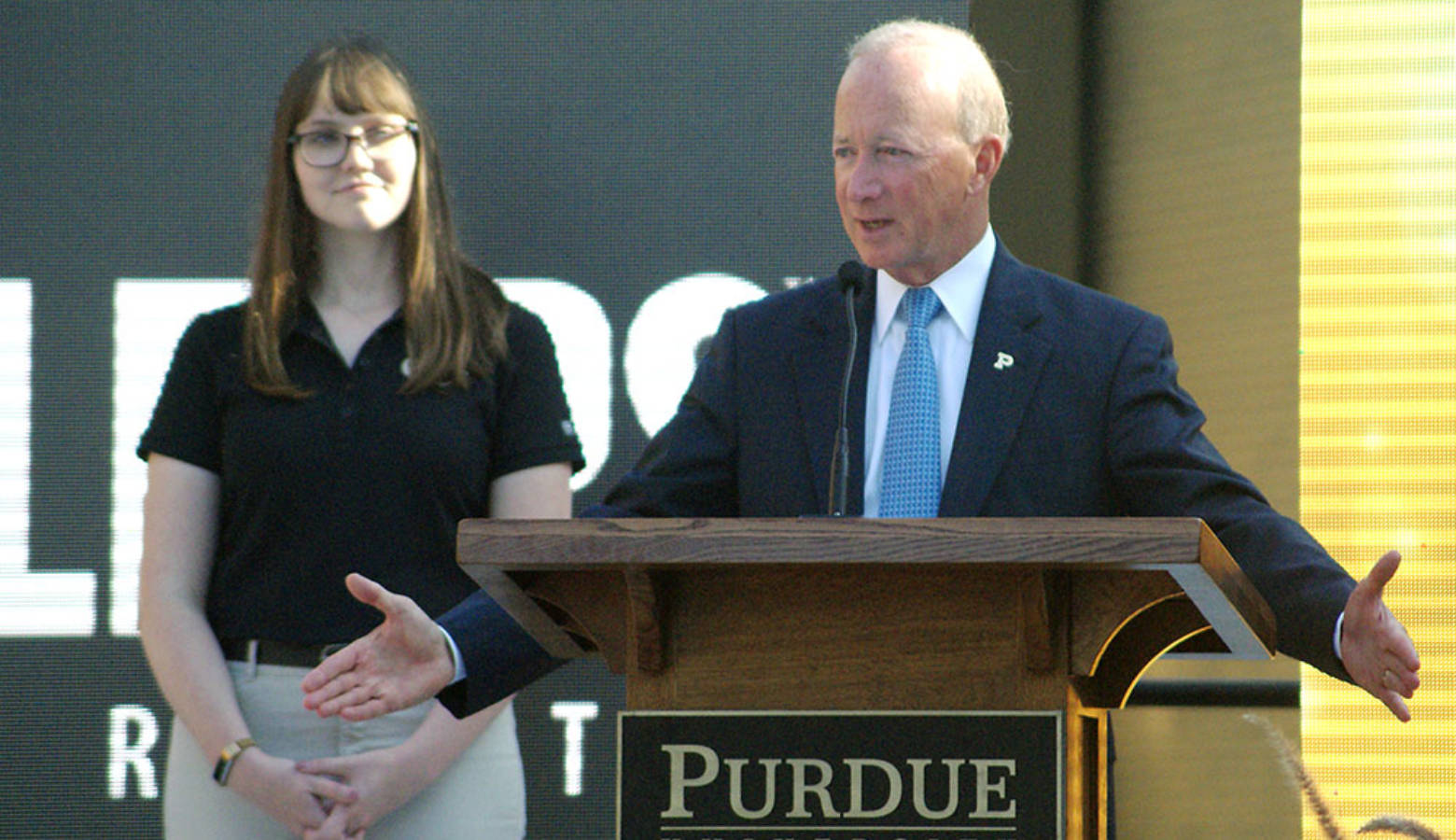 Purdue President Mitch Daniels, with senior Michaela Rumple standing to his left, tells attendees what the new Engineering and Polytechnic Gateway Complex will mean for students and businesses. (Samantha Horton/IPB News)