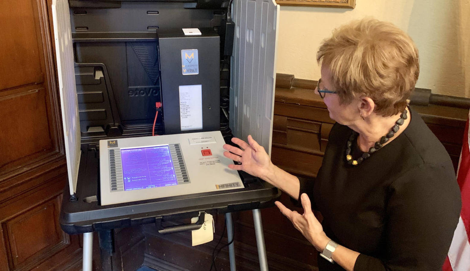 Secretary of State Connie Lawson demonstrates the use of a paper audit trail on an electronic voting machine. (Brandon Smith/IPB News)
