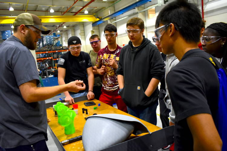 Jeremey Rorie shows Penn High School students what he does for work at B&B Molders in Mishawaka. (Justin Hicks/IPB News)
