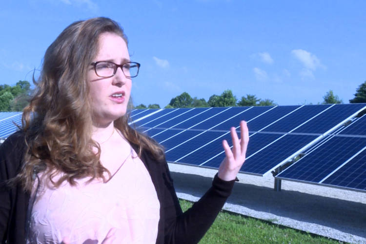 Indiana University student Savannah Rodrigue stands in front of a solar array next to a water booster station in Bloomington which helps to offset some of the station's energy use. (Rebecca Thiele/IPB News)