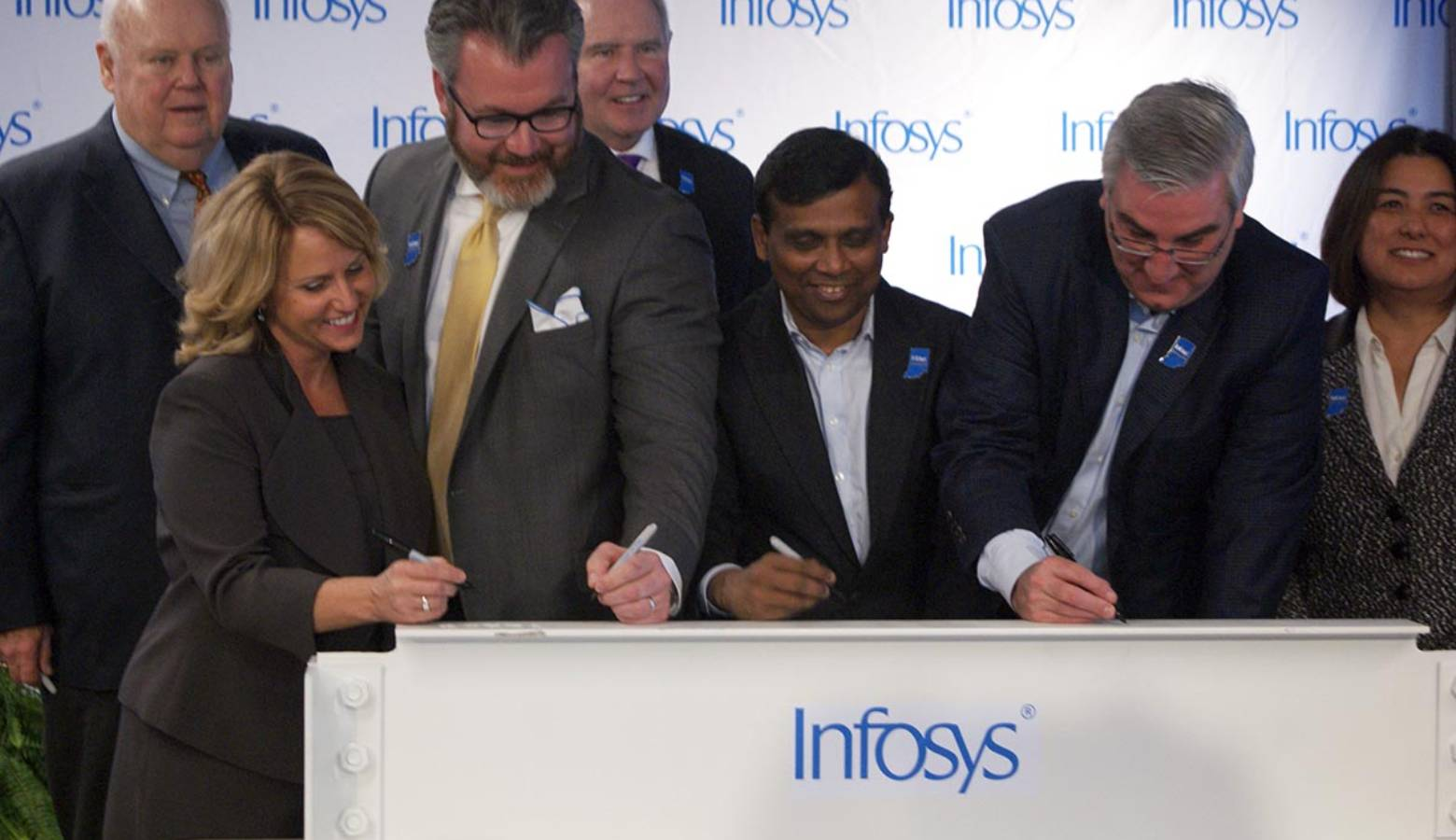 State and local officials along with Infosys company leaders sign a beam commemorating the progress to its U.S. Educational Center in Indianapolis. (Samantha Horton/IPB News)