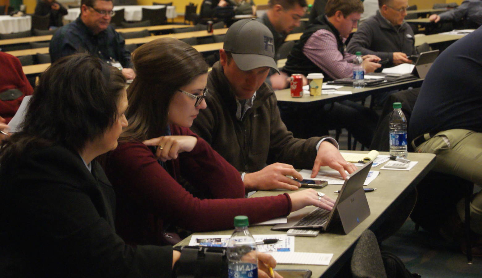 (Left to right) Kayla Holscher, Jenna Lansing and Andy Hruby work as a group during the Ag Survivor simulator activity at Purdue University's Top Farmer Conference. (Samantha Horton/IPB News)