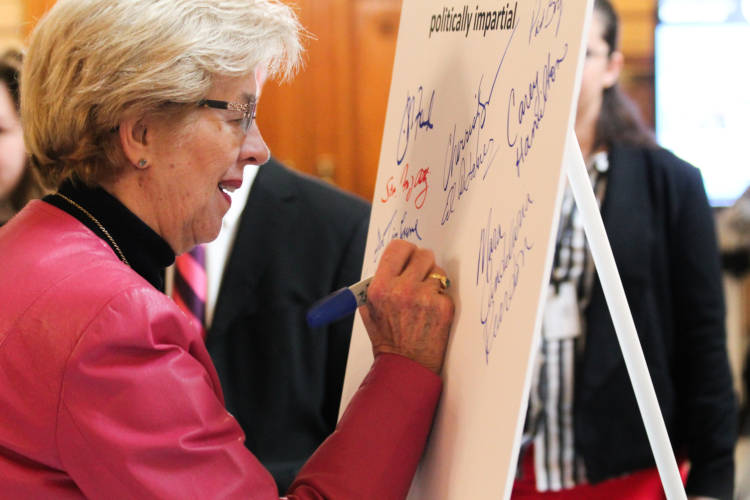 Rep. Sue Errington (D-Muncie) and other lawmakers sign a pledge to support redistricting reform. (Lauren Chapman/IPB News)