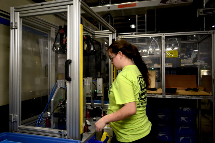 A worker at a factory in North Vernon, Indiana, works with a plastics manufacturing robot. (Justin Hicks/IPB News)