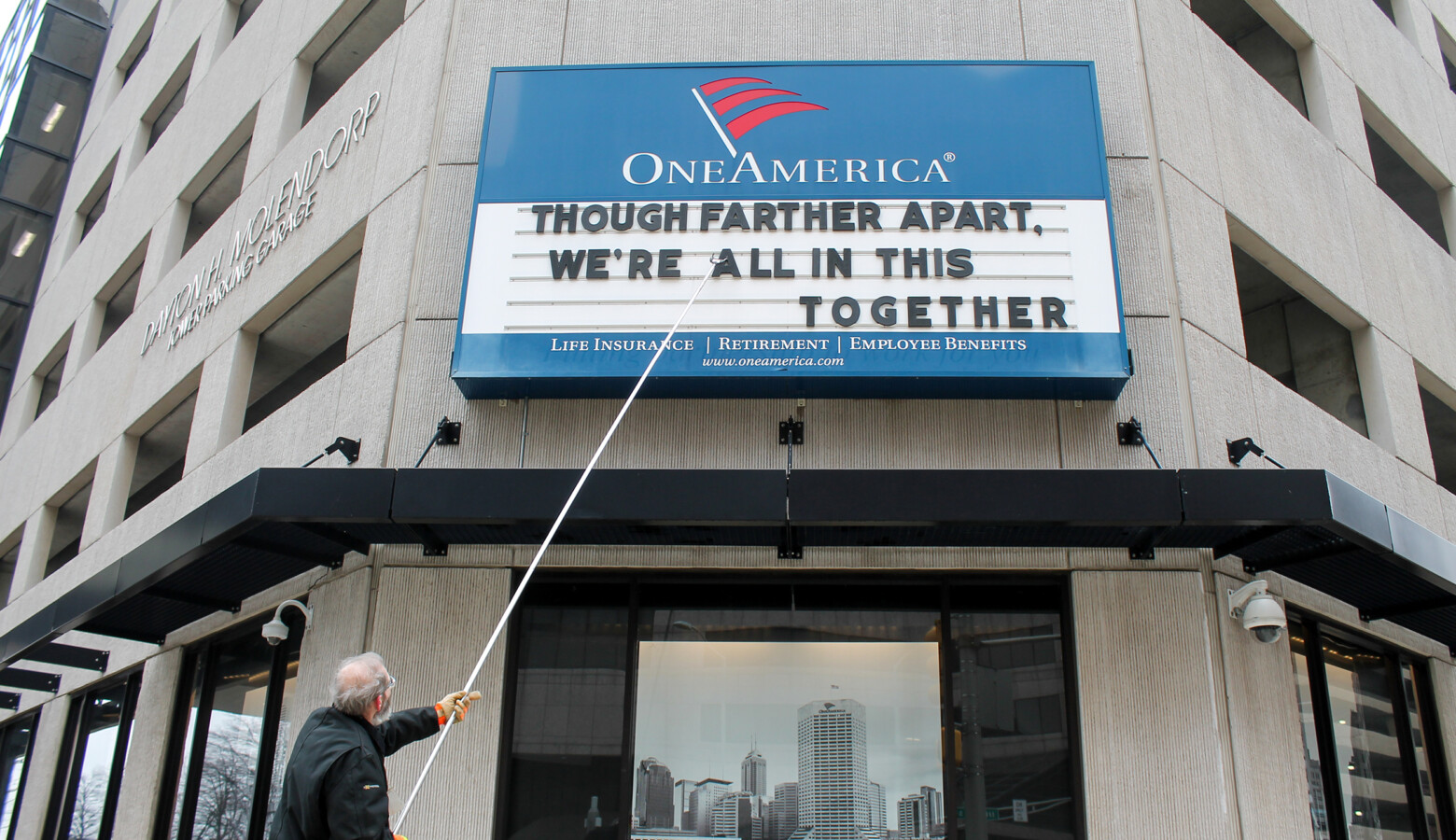 "A man adjusts the One America sign in downtown Indianapolis. It usually displays a pun, but the message shortly before the governor's address reads: ""Although father apart, we're all in this together."" (Lauren Chapman/IPB News)"
