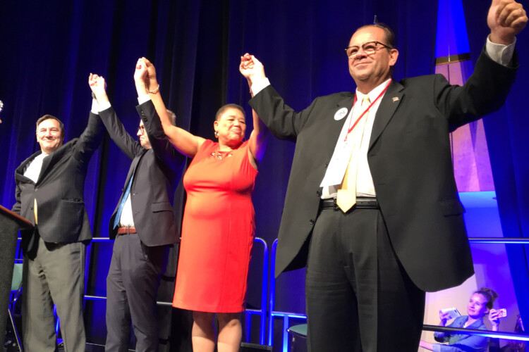 A state party convention staple that will be missing this year: in 2018, Indiana Democrats' statewide candidates joined hands on stage as the convention wrapped up. (FILE PHOTO: Brandon Smith/IPB News)