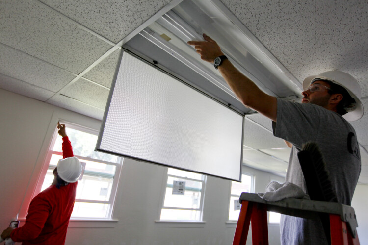 Most of Indiana's clean energy jobs are in energy efficiency. In this photo, Construction workers install new energy-efficient windows and lighting in a naval center in California, 2010 (Greg Vojtko/U.S. Navy)