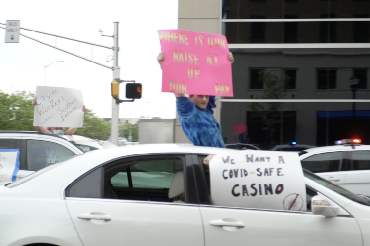 Casino workers hold signs from their cars in downtown Indianapolis. (Alan Mbathi/IPB News)