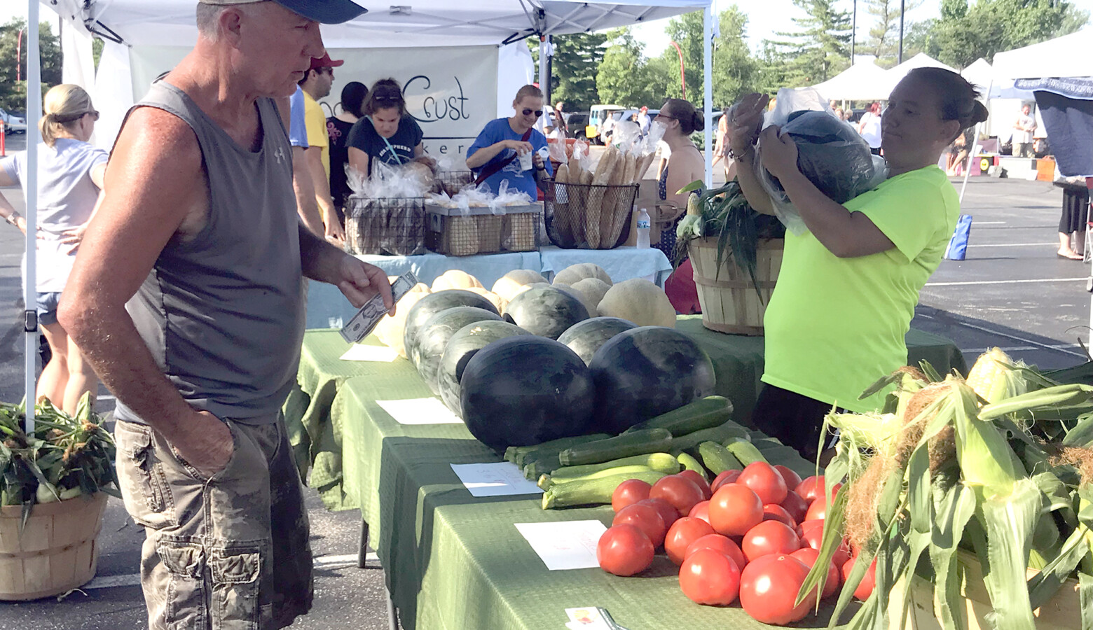 A customer purchases produce at the 2018 Columbus farmers market. (Lauren Bavis/Side Effects Public Media)