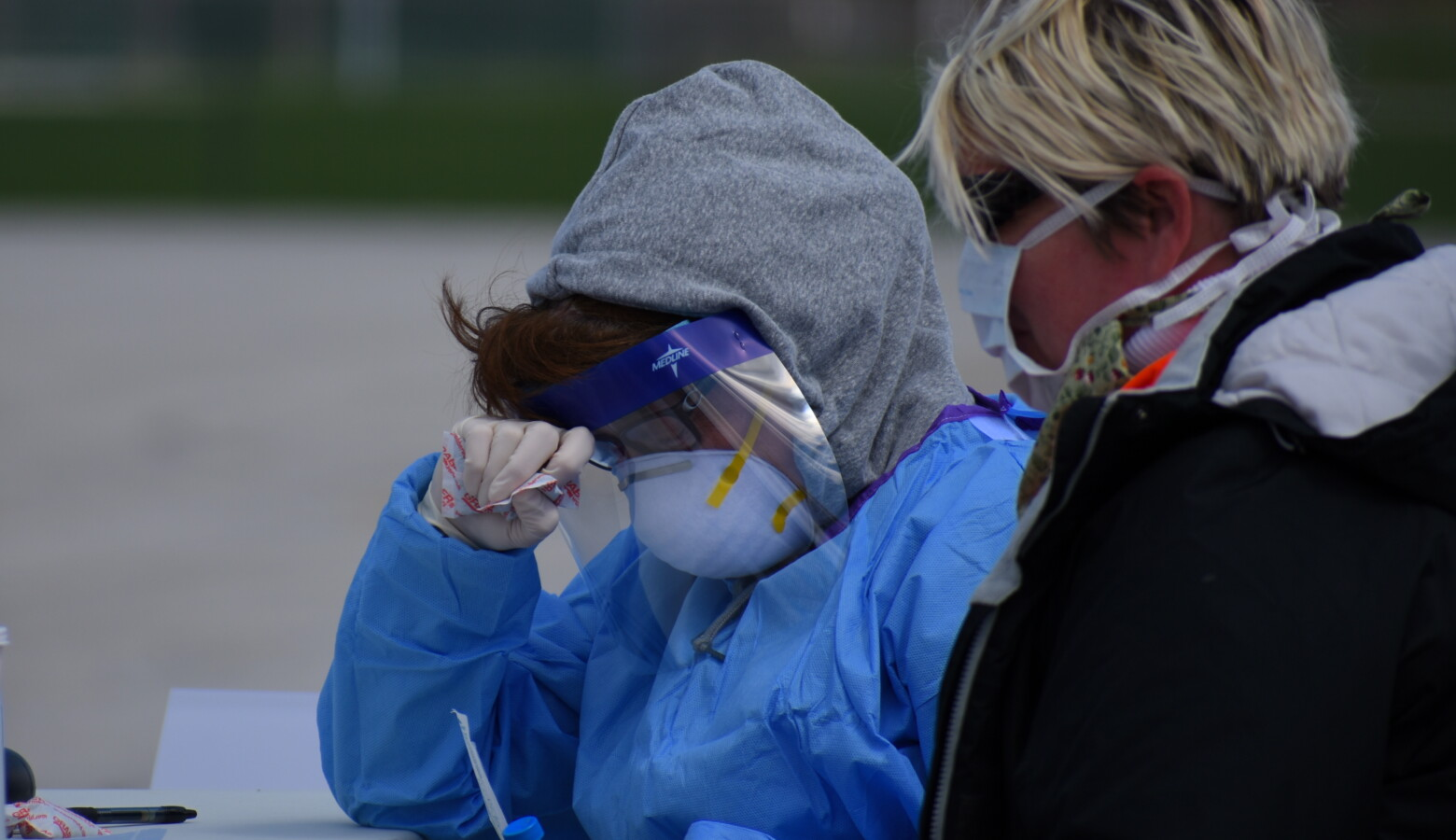 Employees doing COVID-19 testing wear considerable amounts of personal protective equipment. (Justin Hicks/IPB News)