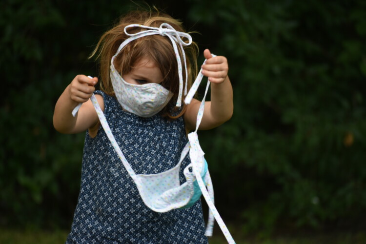 A child plays with a face mask. (Justin Hicks/IPB News)