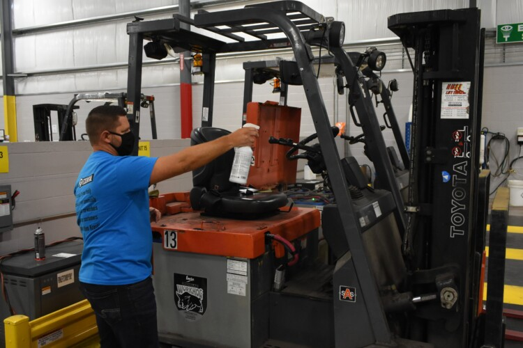 A worker sprays down a forklift in an Elkhart factory in accordance with the company's COVID-19 safety standards. (Justin Hicks/IPB News)