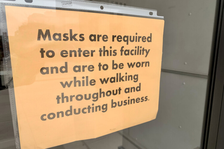 Signs posted at entrances to the Statehouse tell visitors they must wear masks inside. (Brandon Smith/IPB News)