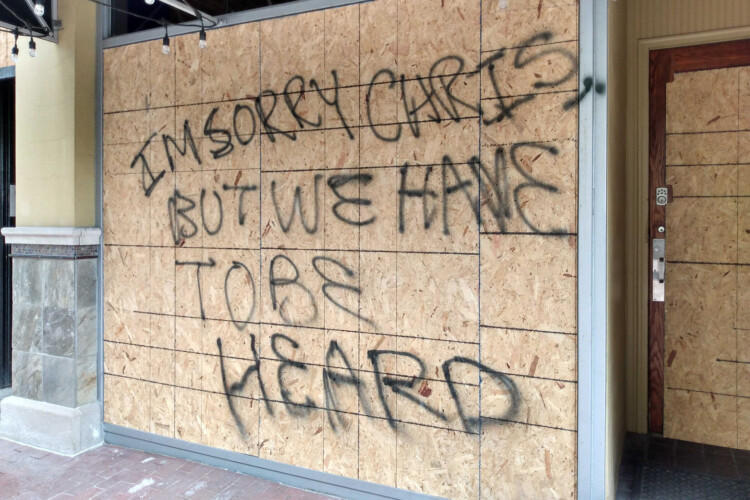 """In Indianapolis, the first business with a broken window was Jack's Donuts, just east of the Statehouse. Protesters left a message for the owner after the clashes with police: """"I'm sorry Chris, but we have to be heard."""" (Lauren Chapman/IPB News)"""