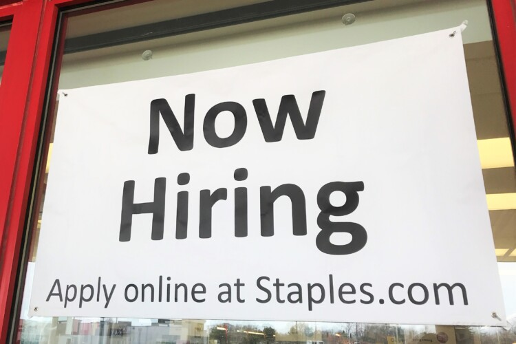 "A ""Now Hiring"" sign on the front of a Staples in Elkhart, Indiana. (Justin Hicks/IPB News)"
