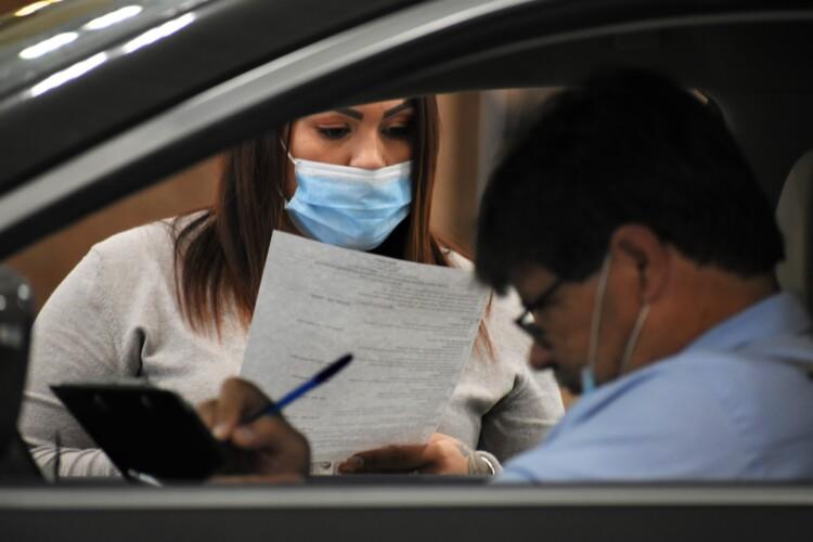 A human resources representative reads a resume at a drive-thru job fair in Elkhart. (Justin Hicks / IPB News)
