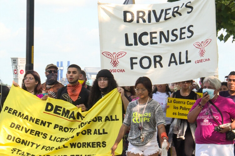 Members of Movimiento Cosecha Indiana march along the White River in Indianapolis, demanding driver's licenses for undocumented Hoosiers. (Lauren Chapman/IPB News)